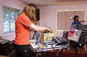 Electronic musician fiddles with his gear